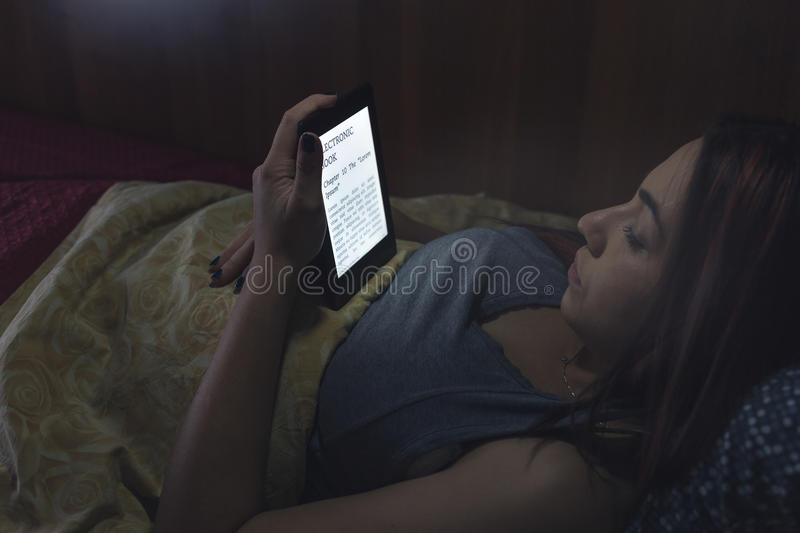 Reading an ebook in bed. During the night, a girl is reading an ebook with her backlit ereader device while she's in bed. Note: Lorem Ipsum text there are no stock photography