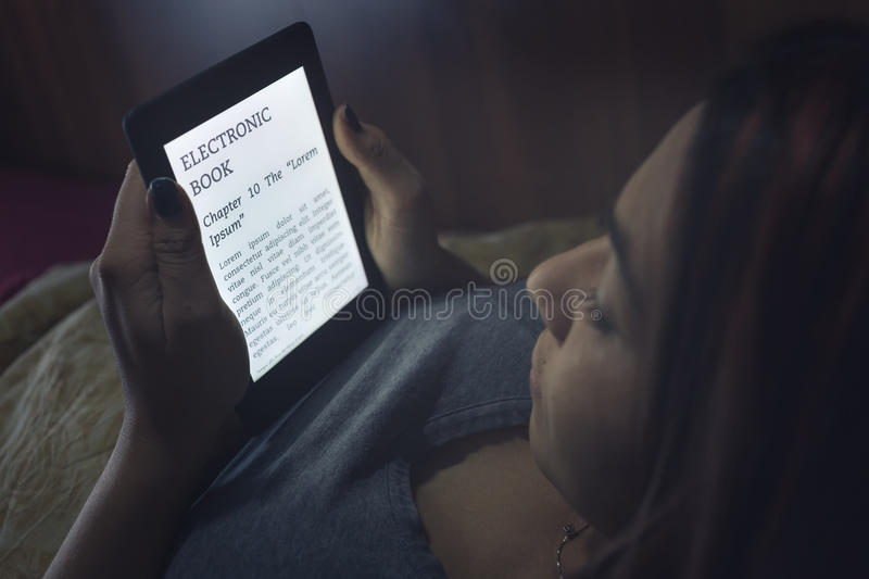 Reading an ebook in bed. During the night, a girl is reading an ebook with her backlit ereader device while she's in bed. Note: Lorem Ipsum text there are no royalty free stock image