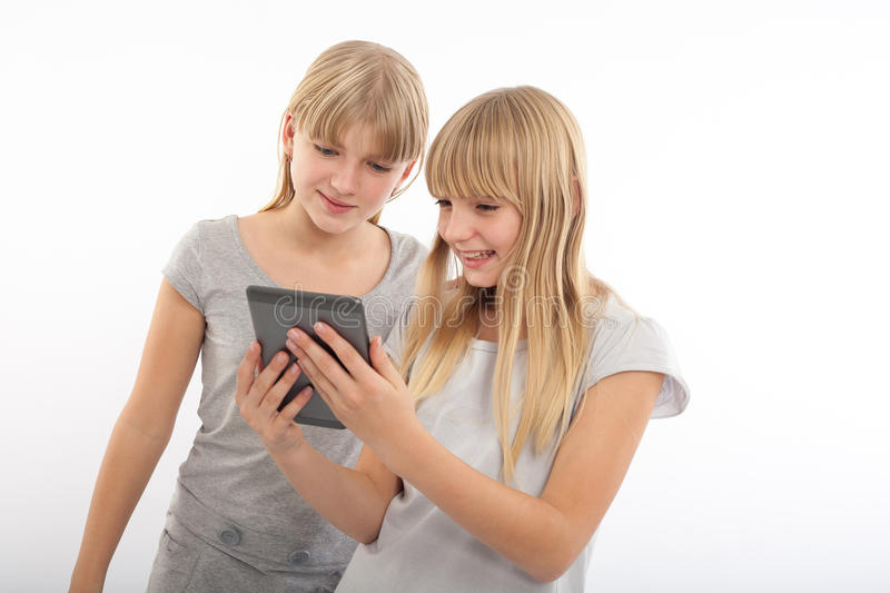 Reading an ebook. Girls reading a funny ebook with a tablet device in front of a white background stock photos