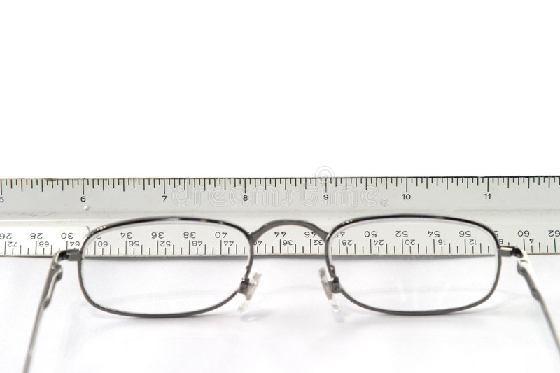 Reading eyeglasses on table with view of ruler through glasses. Reading eyeglasses and ruler placed on table; the glasses are in the foreground and are out of stock photo
