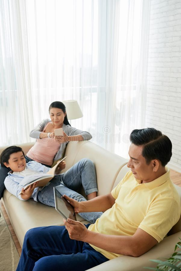 Reading family. Asian family reading books in paper cover and online when resting at home stock images