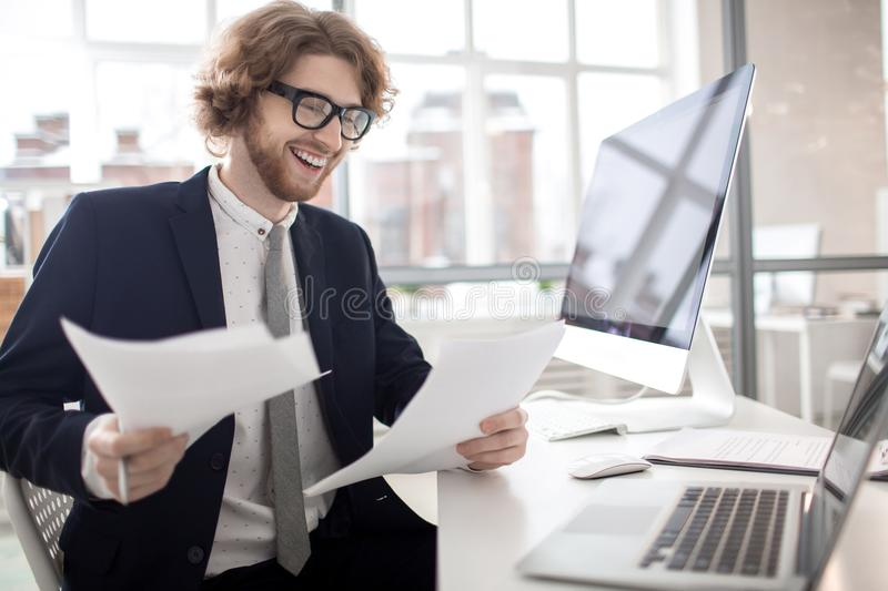 Reading financial papers. Happy young financier reading documents or new contracts in office stock images