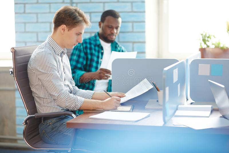 Reading financial papers. Serious young financier reading papers by individual workplace in working environment stock image