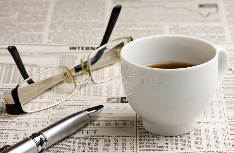 Glasses Coffee and Pen on the Newspaper stock photo