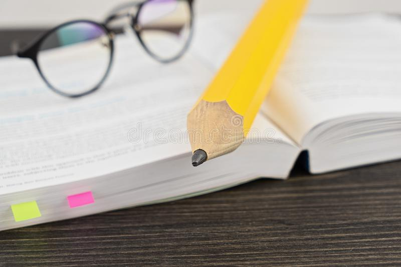 Reading glasses on an open book with big yellow pencil. DOF Shallow Depth of Field and selective soft focus. Workbook and exam concept royalty free stock image