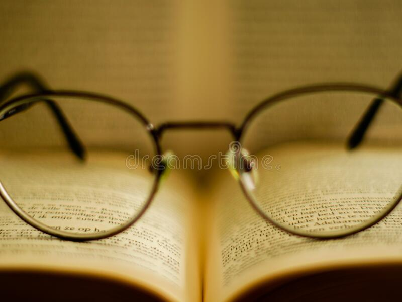 Reading glasses reading a book stock photo