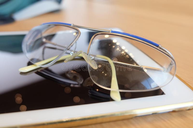 Reading Glasses with Tablet Computer on Table. Beautiful Reading Glasses with Tablet Computer on The Wooden Table in A Working Day stock photo