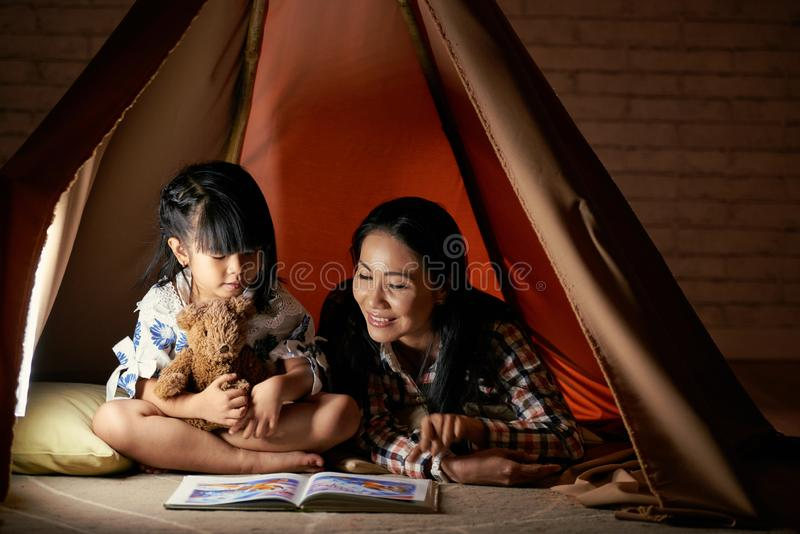Reading before going to bed. Mother reading a story to daughter in the evening stock photos