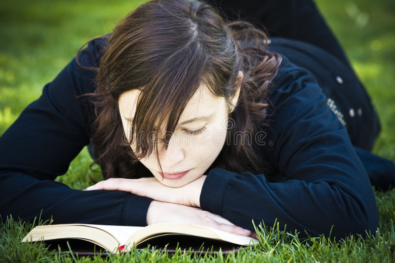 Reading on the grass. Beautiful brunette woman reading on the grass royalty free stock photo