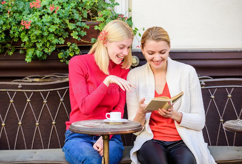 Reading inspiring book. Self improvement and education. Discussing popular bestseller book. Book every girl should read. Girls friends sitting cafe terrace royalty free stock photography