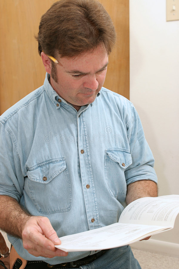 Reading Instructions. A handyman reading instructions stock image