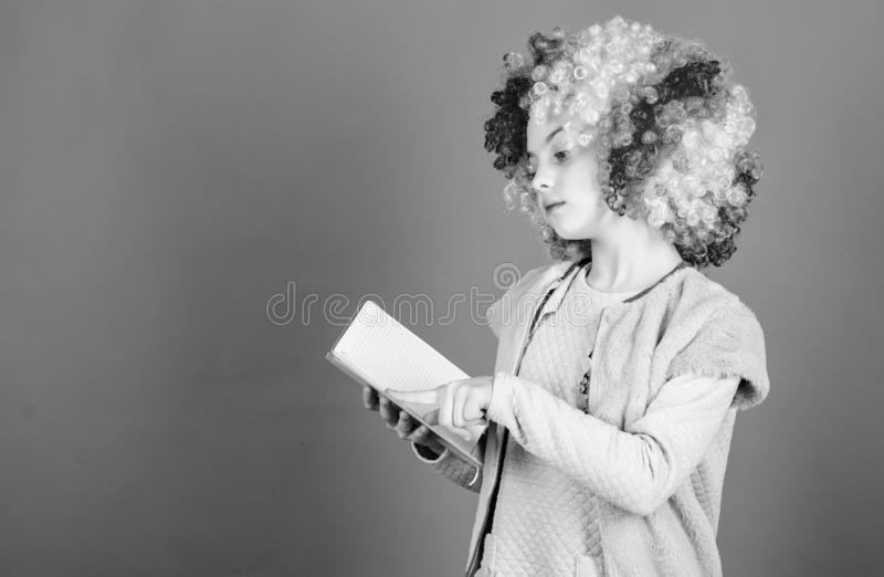 Reading jokes. Time to have fun. Circus school. Study hard. Ridiculous story. Reading funny book. Literature club. Jokes. Book concept. Kid colorful curly wig stock photography