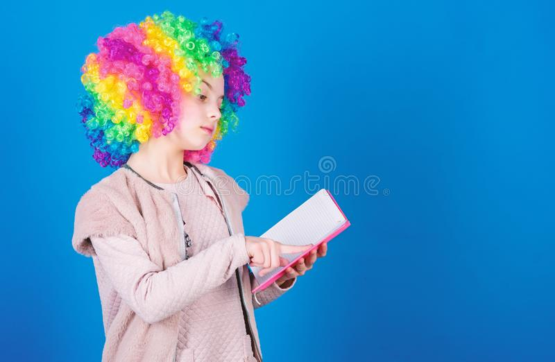 Reading jokes. Time to have fun. Circus school. Study hard. Ridiculous story. Reading funny book. Literature club. Jokes. Book concept. Kid colorful curly wig stock image