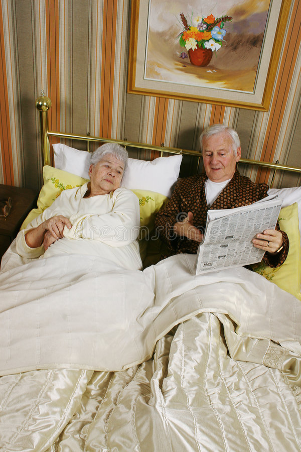 Reading the latest news. Old couple in a bed reading latest news stock image