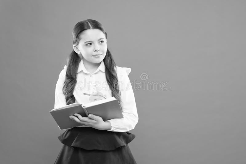 Reading lesson. Happy child enjoy study and reading book. back to school. get information form book. small girl at. School lesson. schoolgirl writing notes on royalty free stock image