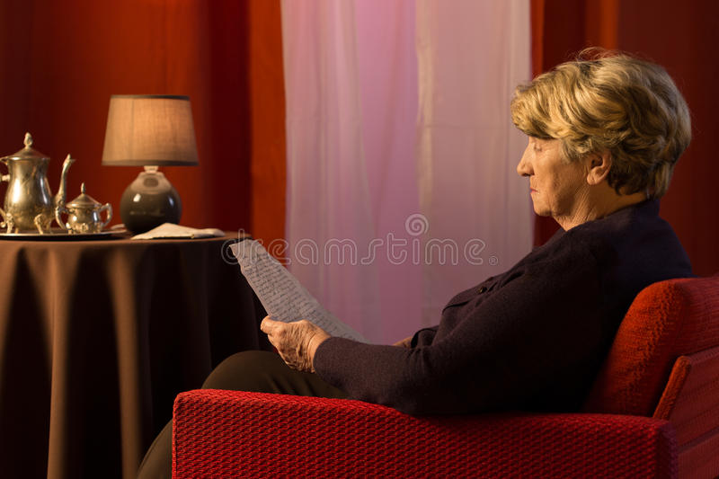 Reading the letter. Photo of aged lonely sad woman reading the old letter stock photos