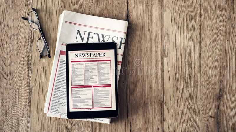 Reading news on tablet and newspaper on wooden background royalty free stock photos