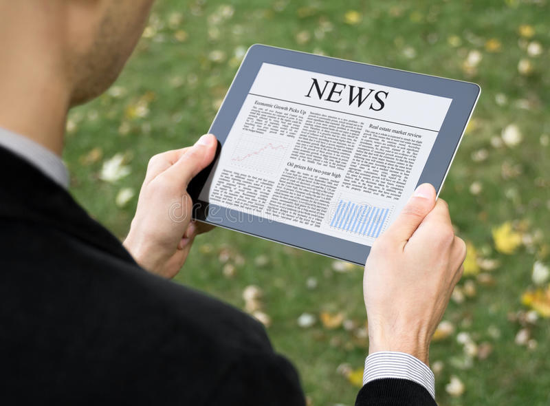 Reading News On Tablet PC. Businessman reading news on digital tablet at park