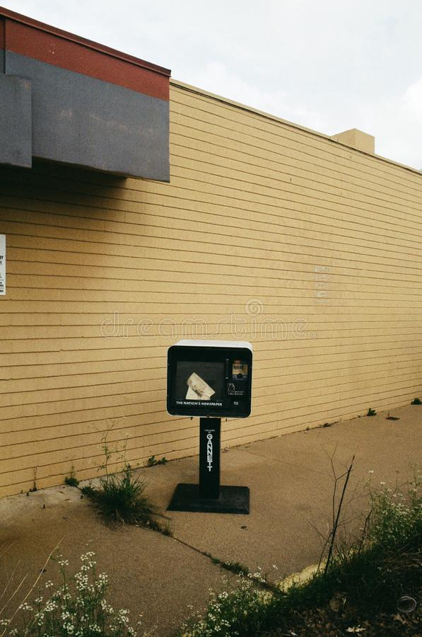 Reading the news. WACO, UNITED STATES - Jun 19, 2019: A film photo of a abandoned news paper stand royalty free stock photography