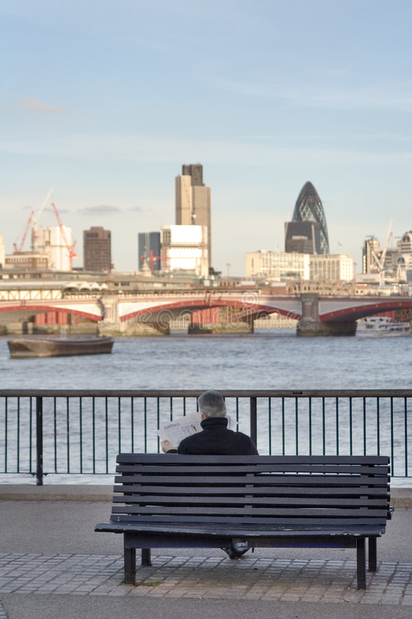 Reading newspaper. Grey haired man sitting on a bench reading newspaper facing London cityscape from a Thames river Southern Bank royalty free stock image