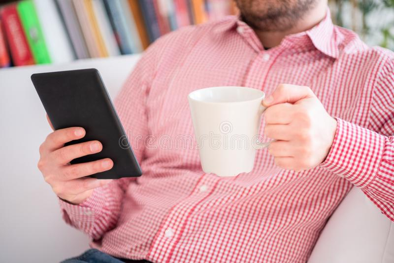 Reading a novel bestseller on ebook reader at home stock photo