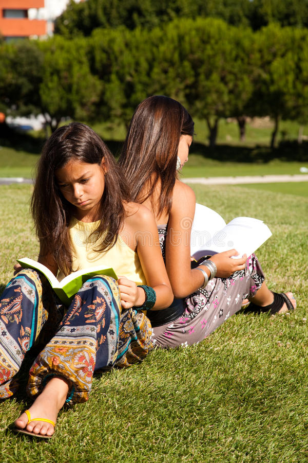 Reading at the park. Two young sisters at the park reading a book royalty free stock photo