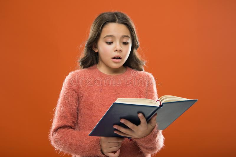 Reading practice for kids. Childrens literature. Girl hold book read story over orange background. Child enjoy reading royalty free stock photography