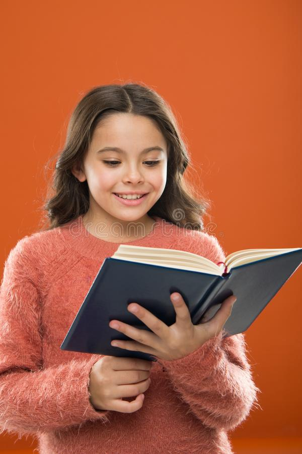 Reading practice for kids. Girl hold book read story over orange background. Child enjoy reading book. Book store royalty free stock photography