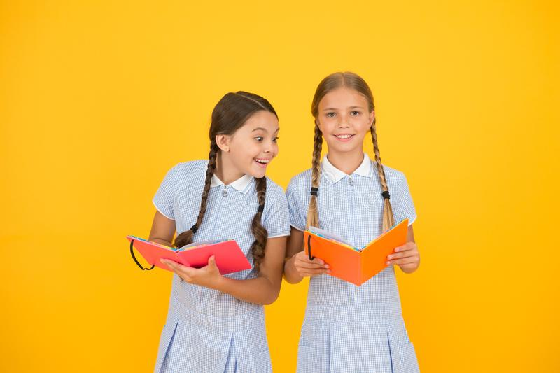 Reading and retelling. Small children holding books yellow background. Sincere interest. Little girls with encyclopedia royalty free stock photos