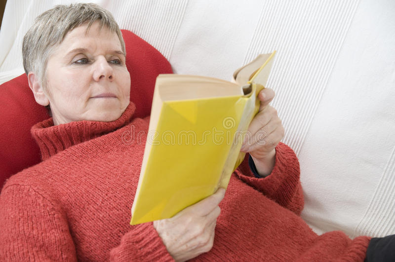 Reading On The Settee Bed Stock Photos