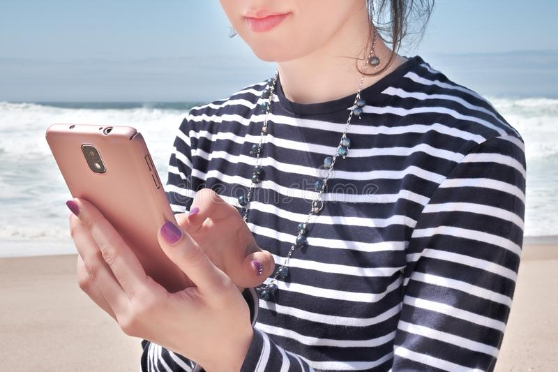 Reading in smartphone on beach, summer day stock photography