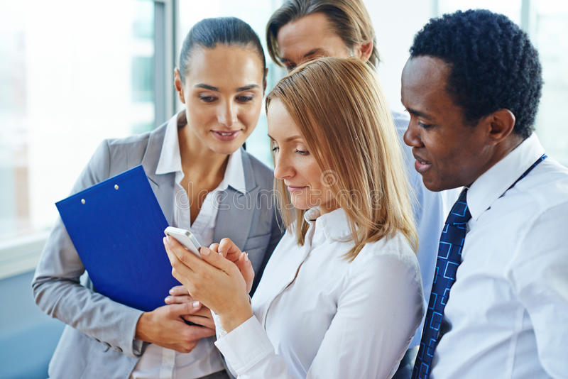 Reading sms. Businesswoman with cellphone and her colleagues reading sms royalty free stock images