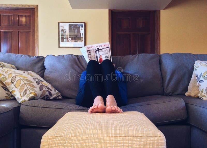 Reading on sofa stock photography