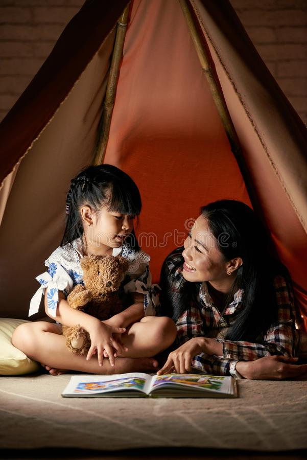 Reading story book. Asian women reading fairytale to her little daughter stock image
