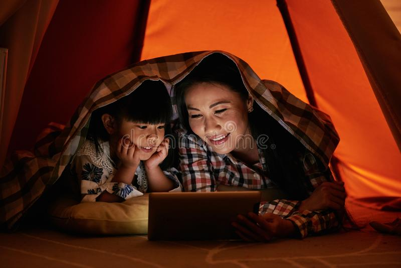 Reading story. Smiling Asian women reading e-book to her little daughter stock photos