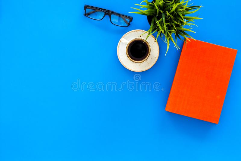 Reading for study and work. Self-education concept. business literature. Books with empty cover near glasses, coffe. Plant on blue desk top view stock images