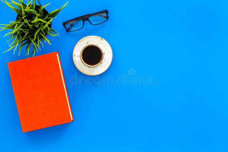 Reading for study and work. Self-education concept. business literature. Books with empty cover near glasses, coffe. Plant on blue desk top view stock photos