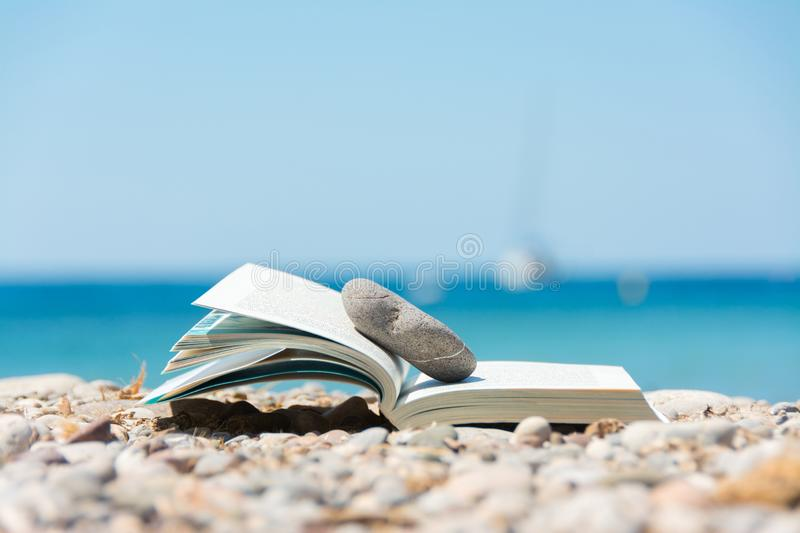 Reading in summer vacation, concept. Book on the pebble beach x royalty free stock photos