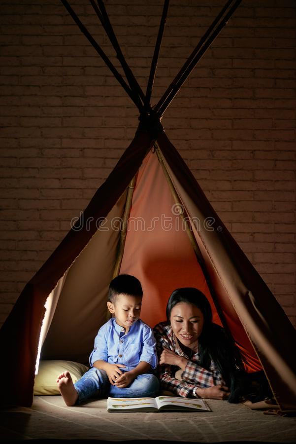 Reading to son. Asian women reading a story to her little son stock images