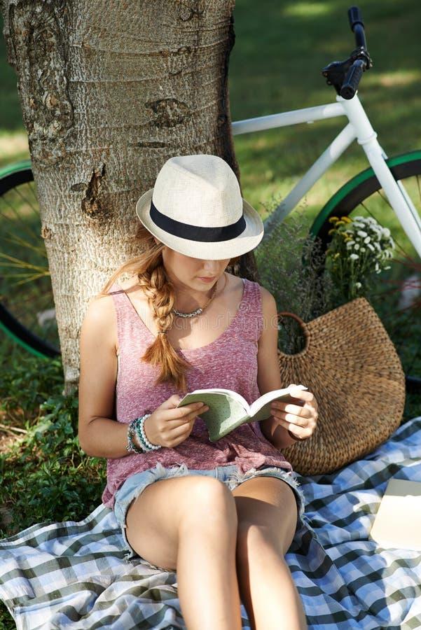 Reading under the tree stock photo