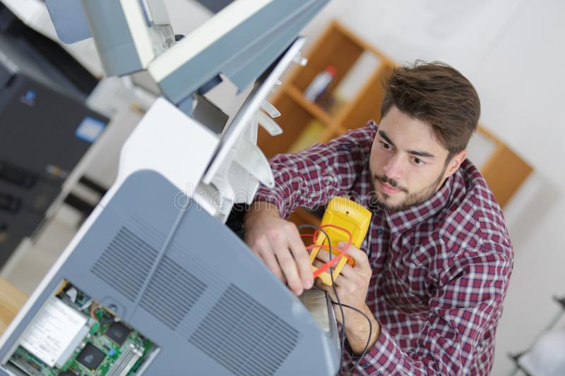 Reading the volt reader. Technician stock photography
