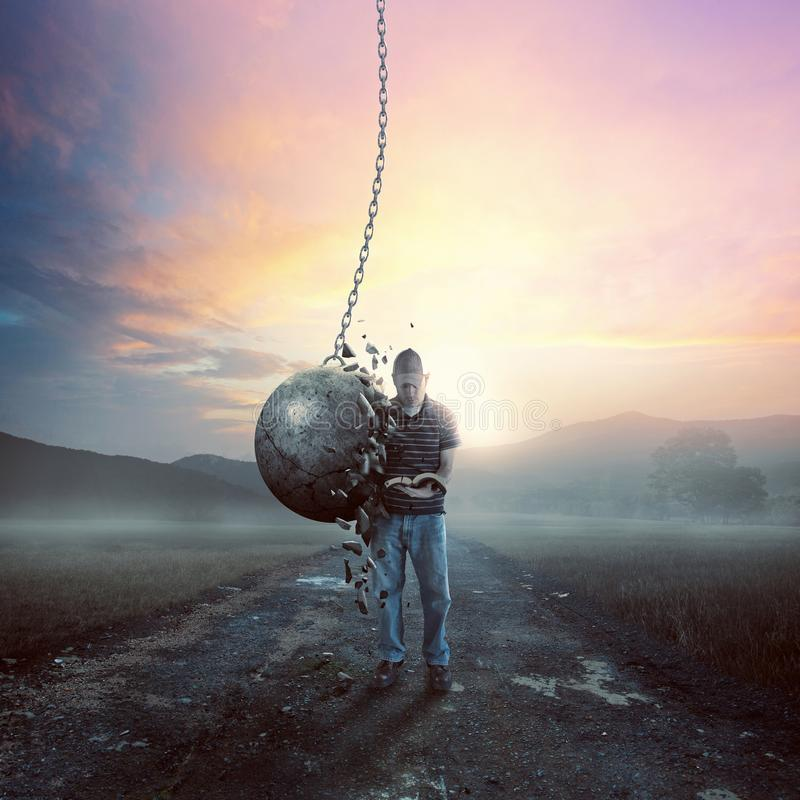 Reading and wrecking ball. A man reads his Bible but is not moved by a large wrecking ball royalty free stock photos