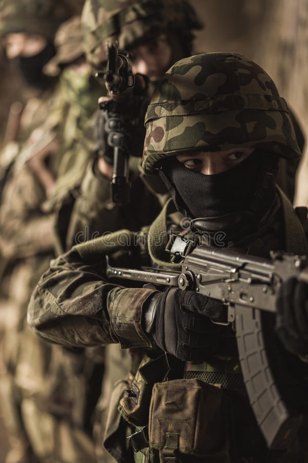 Ready for action. Group of armed soldiers during intense training exercise royalty free stock photography