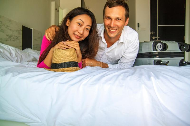 Ready for adventures. Young couple preparing for honeymoon, lying on bed with travel suitcase. stock image