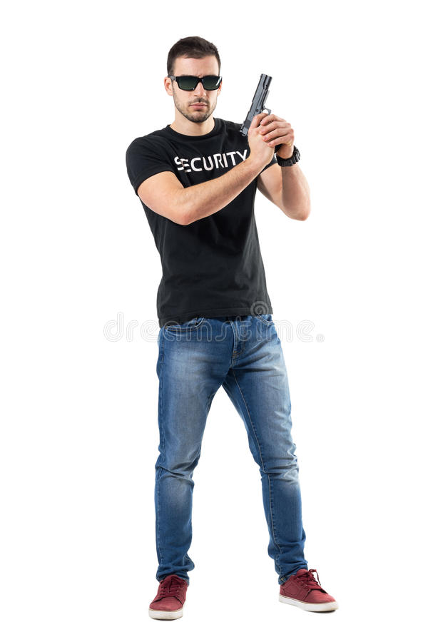 Ready alerted undercover officer holding gun in both hands looking at camera royalty free stock photo