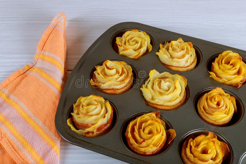 Baked potato roses with a bacon in oven pan royalty free stock image