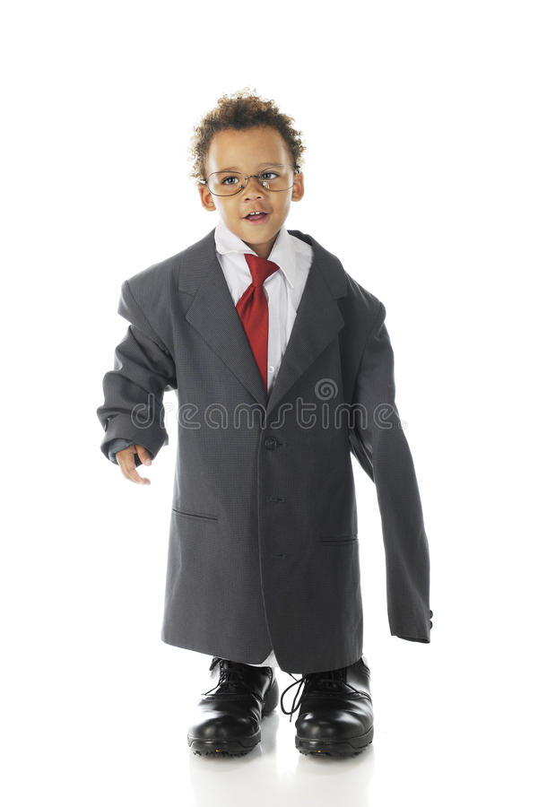 Ready for Business. An adorable tot happily dressed in an oversized suit jacket, shirt and tie with his daddy's dress shoes. On a white background royalty free stock image