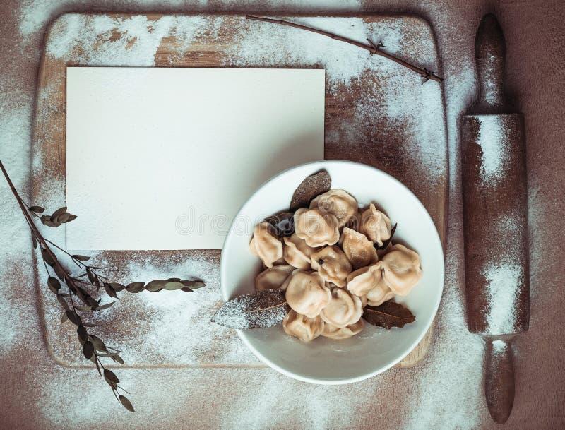 Ready dumplings in a plate on a wooden board royalty free stock photo