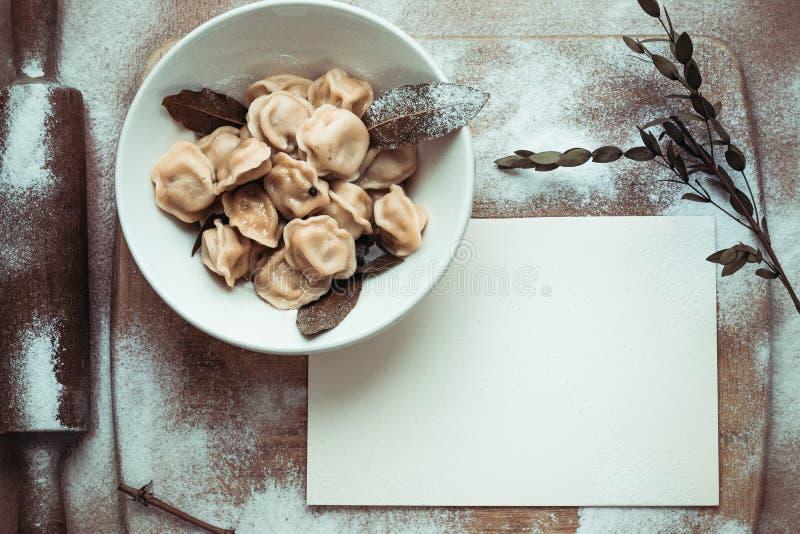 Ready dumplings in a plate on a wooden board stock photo