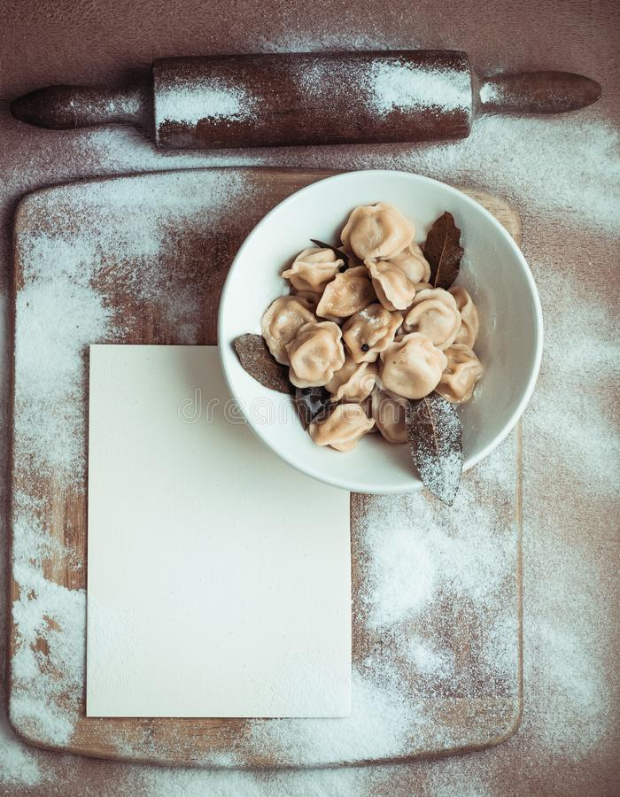 Ready dumplings in a plate on a wooden board stock image
